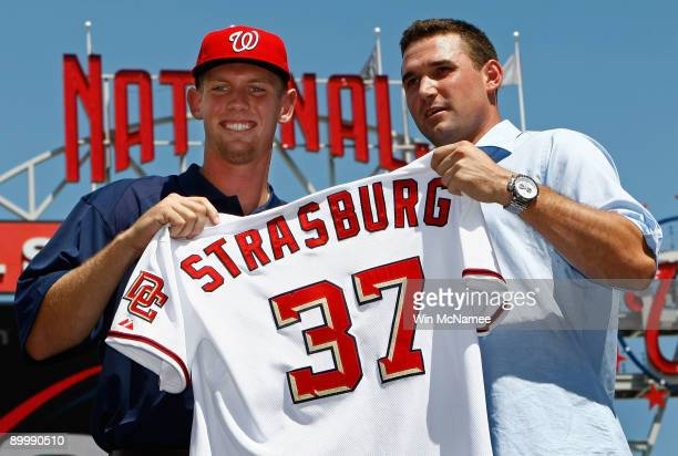 Stephen Strasburg the overall first pick in the 2009 MLB Draft is presented with his jersey by Nationals third baseman Ryan Zimmerman after being...