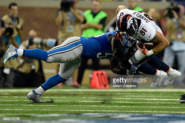 Stephen Tulloch of the Detroit Lions tackles Owen Daniels of the Denver Broncos during the first half of play at Ford Field The Detroit Lions hosted...