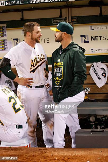 Stephen Vogt and Cody Ross of the Oakland Athletics talk in the dugout during the game against the Los Angeles Angels of Anaheim at Oco Coliseum on...