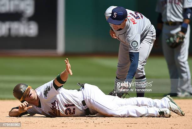 Stephen Vogt of the Oakland Athletics calls timeout after he slides into second base with a double beatting the tag of Brad Miller of the Seattle...