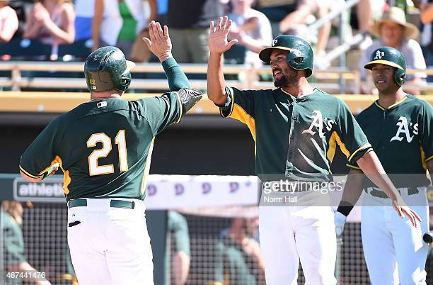 Stephen Vogt of the Oakland Athletics celebrates with teammate Marcus Semien after hitting a thirdinning home run against the Chicago Cubs in a...
