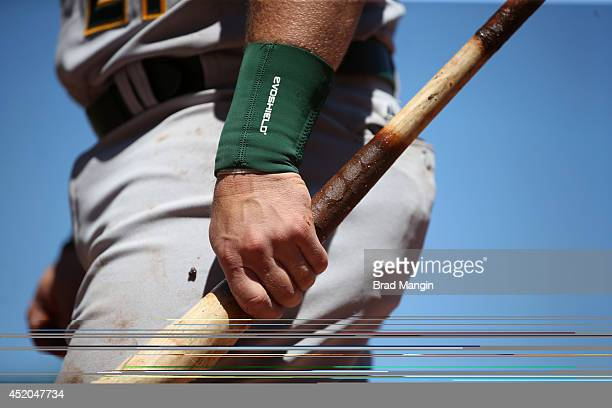Stephen Vogt of the Oakland Athletics grips his bat with his bare hands and pine tar in the on deck circle during the game against the San Francisco...