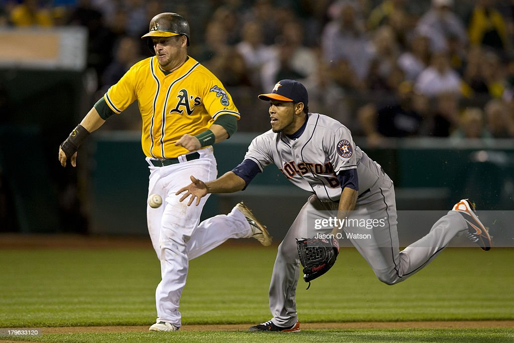 Stephen Vogt #21 of the Oakland Athletics runs past Jorge De Leon #67 of the Houston Astros to score a run during the eighth inning at O.co Coliseum on September 5, 2013 in Oakland, California.