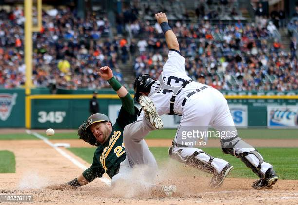 Stephen Vogt of the Oakland Athletics slides into home plate to score a run in the fourth inning against Alex Avila of the Detroit Tigers during Game...