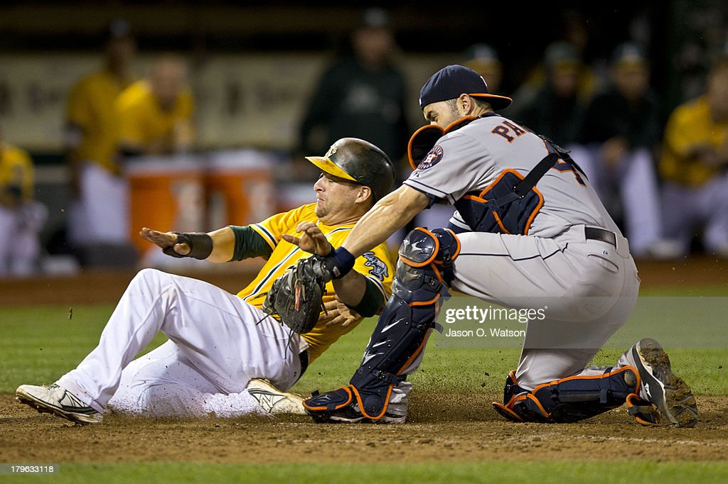 Stephen Vogt #21 of the Oakland Athletics slides past Matt Pagnozzi #44 of the Houston Astros to score a run during the eighth inning at O.co Coliseum on September 5, 2013 in Oakland, California.