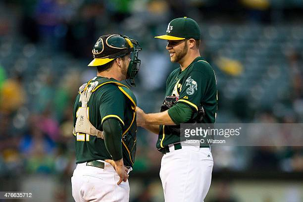 Stephen Vogt of the Oakland Athletics talks to Jesse Hahn during the third inning against the Texas Rangers at Oco Coliseum on June 10 2015 in...