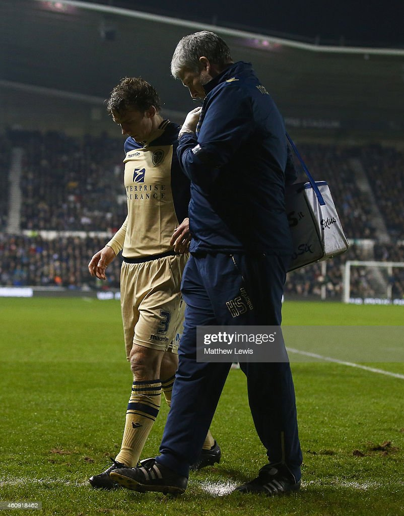 Stephen Warnock of Leeds United is helped off the pitch, after a challenge from Cyrus Christie of Derby County during the Sky Bet Championship match between Derby County and Leeds United at Pride Park Stadium on December 30, 2014 in Derby, England.