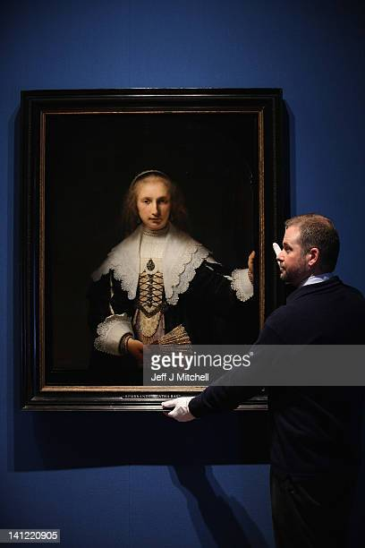 Stephen Webster Exhibition coordinator stands next to the painting Agatha Bas by Rembrandt part of the Royal Collection on display at the Queens...