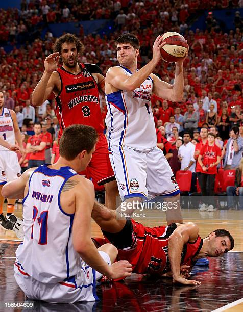 Stephen Weigh of the 36'ers rebounds against Matt Knight and Kevin Lisch of the Wildcats during the round seven NBL match between the Perth Wildcats...