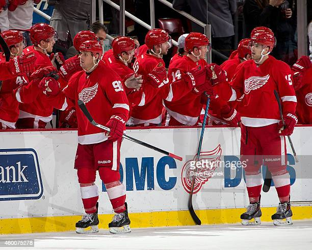 Stephen Weiss and Riley Sheahan of the Detroit Red Wings skate by the bench after their line scored a goal during a NHL game against the New York...