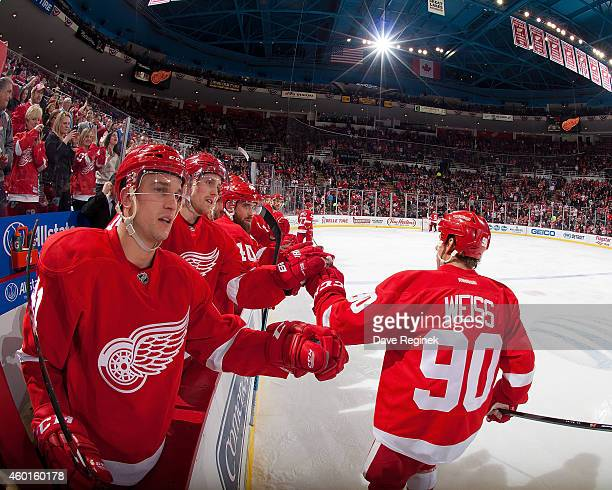 Stephen Weiss of the Detroit Red Wings pounds gloves with Luke Glendening Joakim Andersson and Henrik Zetterberg after a goal during a NHL game...