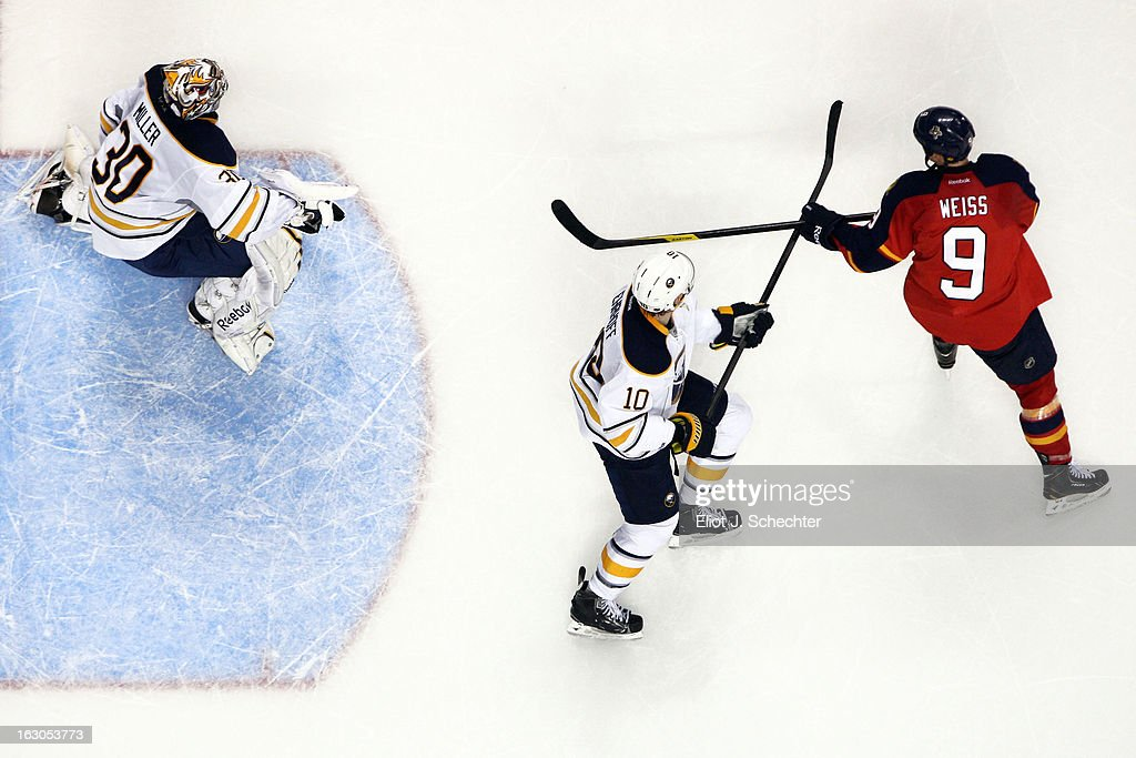 Stephen Weiss #9 of the Florida Panthers crosses sticks with Christian Ehrhoff #10 of the Buffalo Sabres while Goaltender Ryan Miller #30 defends the net at the BB&T Center on February 28, 2013 in Sunrise, Florida.