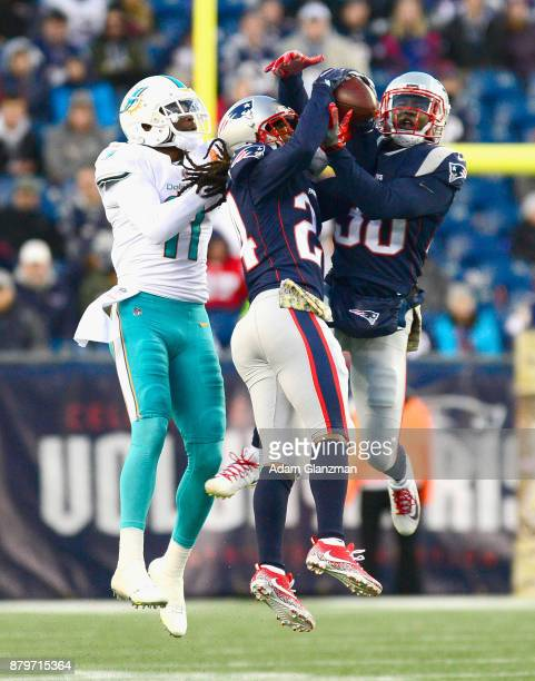 Stephon Gilmore and Duron Harmon of the New England Patriots intercept a pass intended for DeVante Parker of the Miami Dolphins during the fourth...