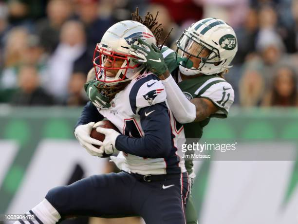 Stephon Gilmore of the New England Patriots intercepts a pass intended for Robby Anderson of the New York Jets on November 25 2018 at MetLife Stadium...