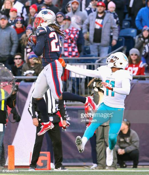 Stephon Gilmore of the New England Patriots intercepts a pass intended for DeVante Parker of the Miami Dolphins during the second quarter of a game...