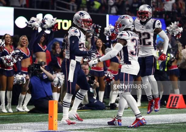 Stephon Gilmore of the New England Patriots is congratulated by his teammates Jason McCourty and Devin McCourty after his fourth quarter interception...