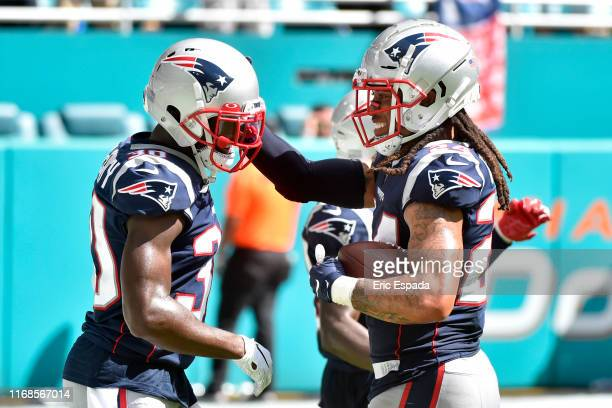 Stephon Gilmore of the New England Patriots is congratulated by Jason McCourty after returning a touchdown in the fourth quarter against the Miami...