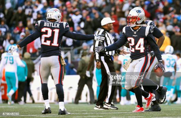 Stephon Gilmore of the New England Patriots reacts with Malcolm Butler after intercepting a pass during the second quarter of a game against the...