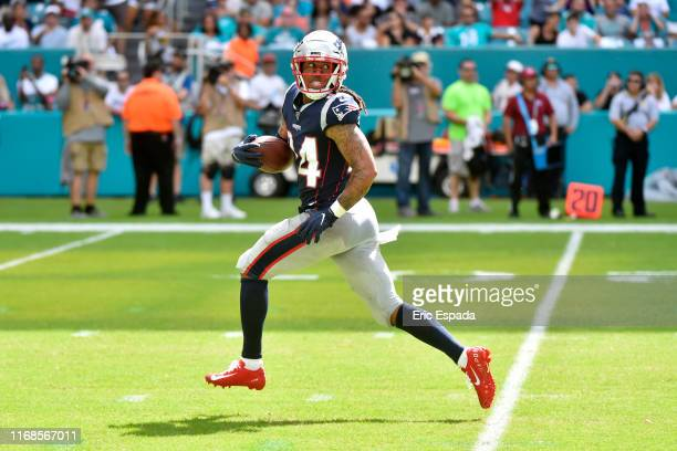 Stephon Gilmore of the New England Patriots returns an interception for a touchdown during the fourth quarter against the Miami Dolphins at Hard Rock...