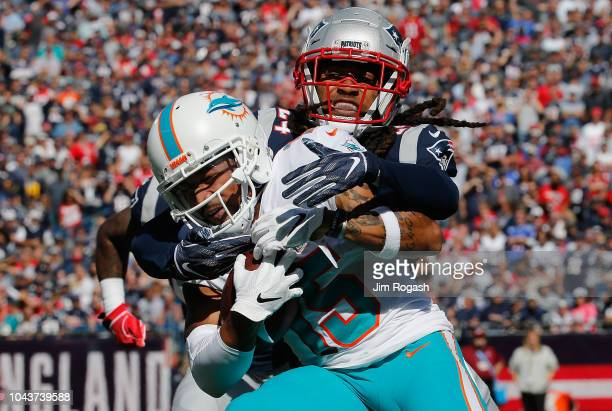 Stephon Gilmore of the New England Patriots tackles Albert Wilson of the Miami Dolphins during the first half at Gillette Stadium on September 30...