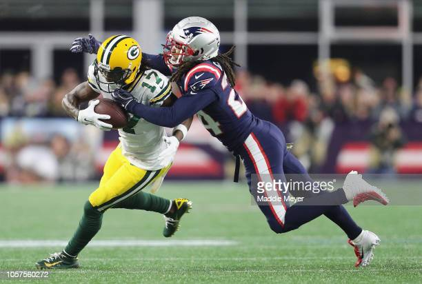 Stephon Gilmore of the New England Patriots tackles Davante Adams of the Green Bay Packers during the first half at Gillette Stadium on November 4...