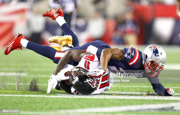 Stephon Gilmore of the New England Patriots tackles Julio Jones of the Atlanta Falcons during the first quarter of a game at Gillette Stadium on...