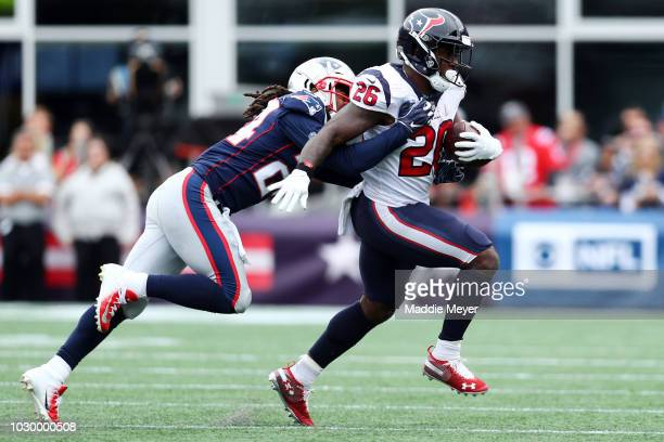 Stephon Gilmore of the New England Patriots tackles Lamar Miller of the Houston Texans on September 9, 2018 at Gillette Stadium in Foxborough,...