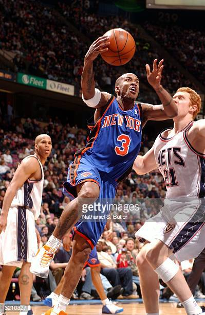 Stephon Marbury of the New York Knicks attempts a layup against Brian Scalabrine and Richard Jefferson of the New Jersey Nets on April 2 2004 at...