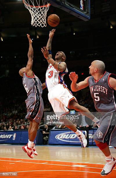 Stephon Marbury of the New York Knicks shoots between Travis Best and Jason Kidd of the New Jersey Nets during their game on April 1 2005 at Madison...