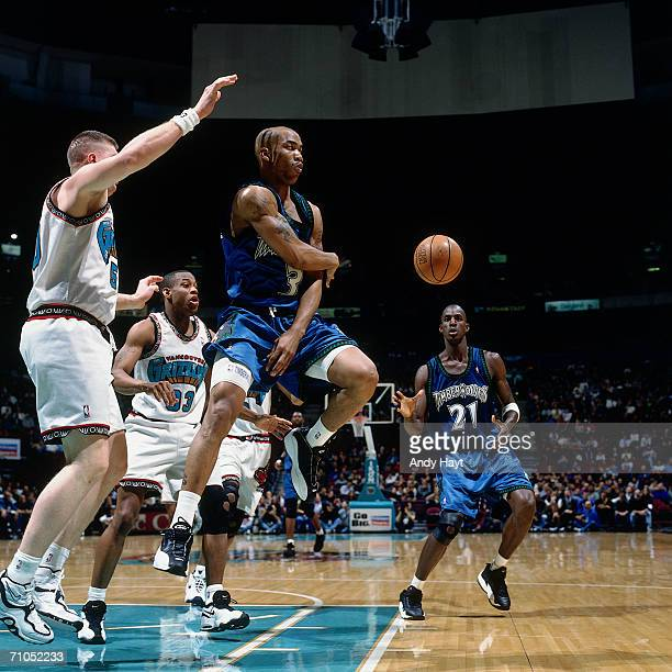 Stephon Marbury passes the ball to teammate Kevin Garnett of the Minnesota Timberwolves during a game against the Vancouver Grizzlies at General...