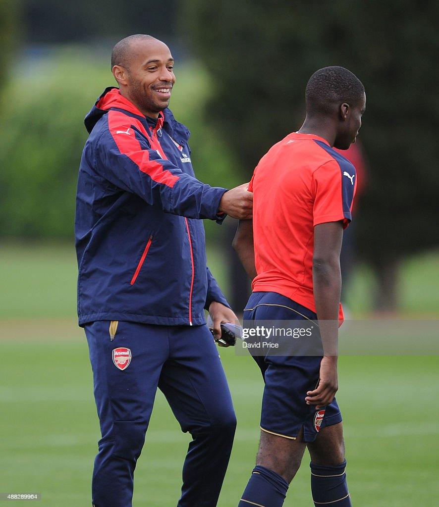 Stephy Mavididi of Arsenal and Thierry Henry assisting with the coaching session during the U19 training session at London Colney on September 15, 2015 in St Albans, England.