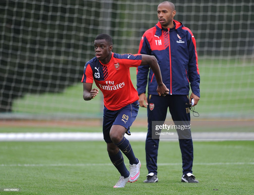 Stephy Mavididi of Arsenal is watched by Thierry Henry during the U19 training session at London Colney on September 15, 2015 in St Albans, England.