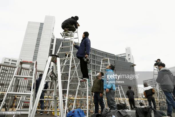 Stepladders are set up in front of the Tokyo Detention House on March 6 as media crews prepare to shoot former Nissan Motor Co Chairman Carlos...