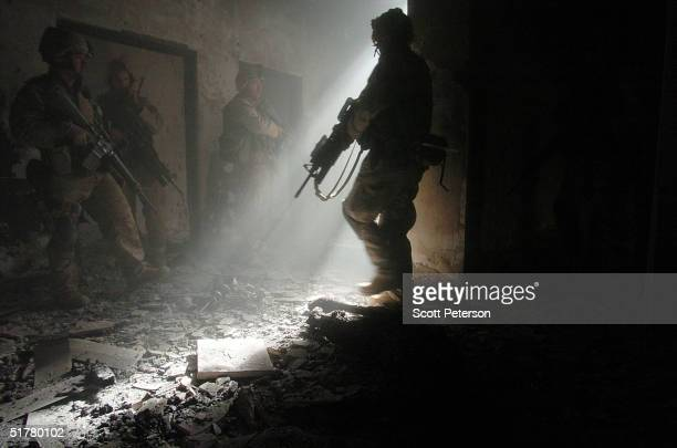 Stepping next to the burnt body of an insurgent US Marines of the Light Armored Reconnaissance company of 1st Battalion 3rd Marines clear houses at...