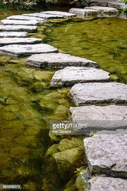 Stepping stones across a pond in Japanese garden