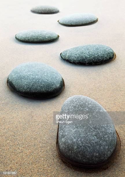 Stepping stones across sand and shallow water, close-up