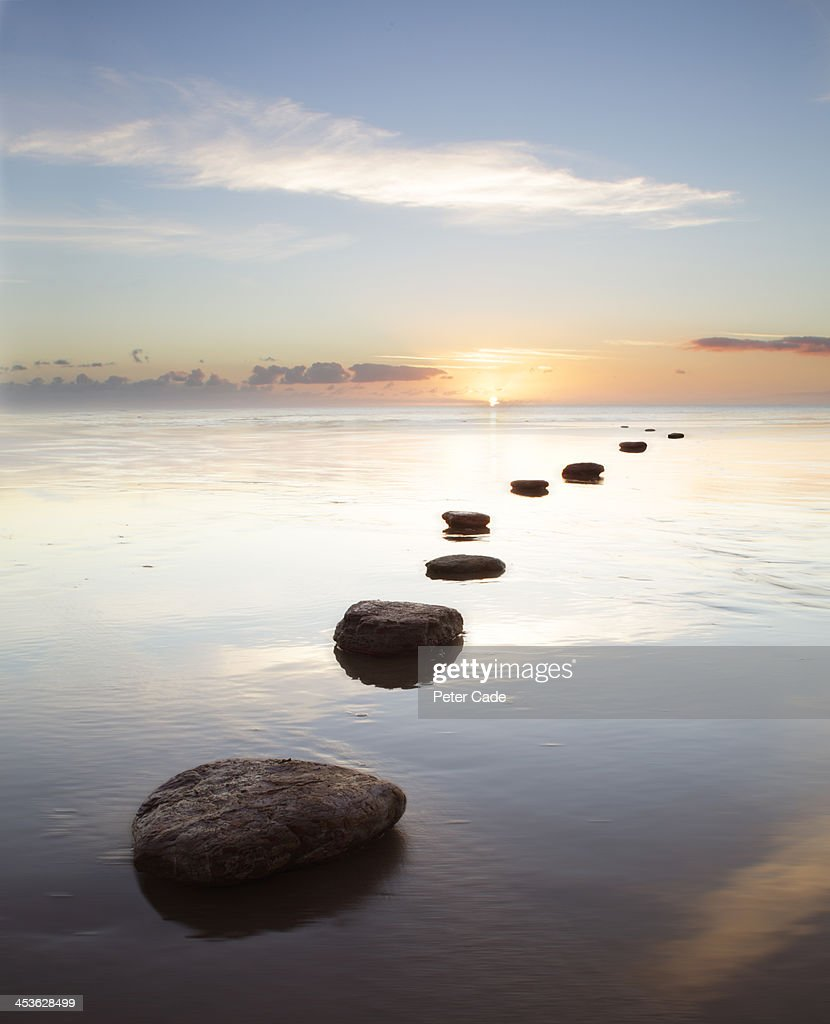 Stepping stones over water at sunrise : Stock Photo