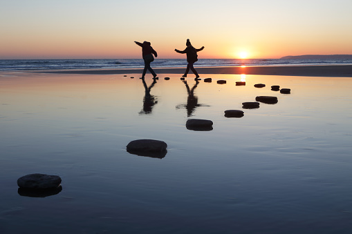 Stepping stones over water, two people - gettyimageskorea