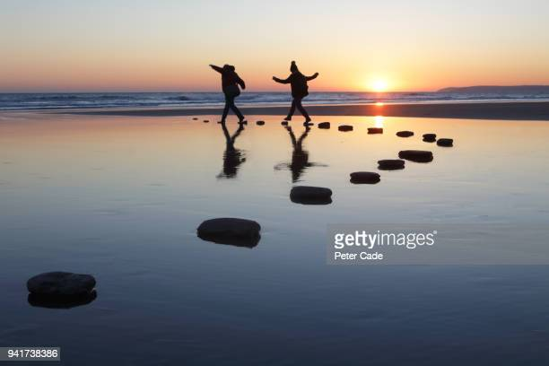 Stepping stones over water, two people