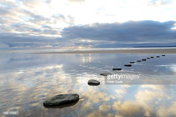 Stepping stones over water with sky reflections