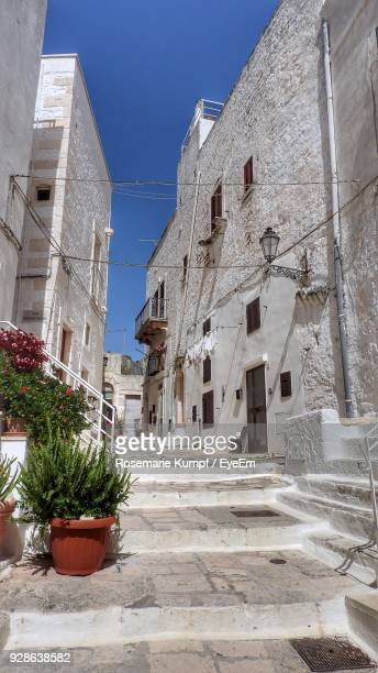 steps amidst buildings in city during sunny day - ostuni stock photos and pictures