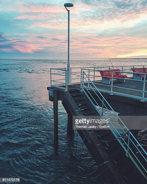 steps by pier in sea against cloudy sky - arcachon stock photos and pictures