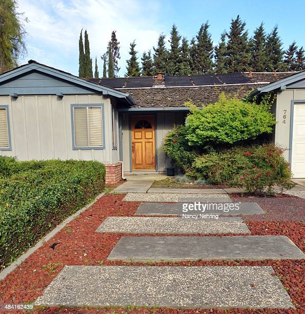 Steps leading to front door add a unusual feature to suburban tract house Solar panels on roof Built about 1970 Sunnyvale California USA