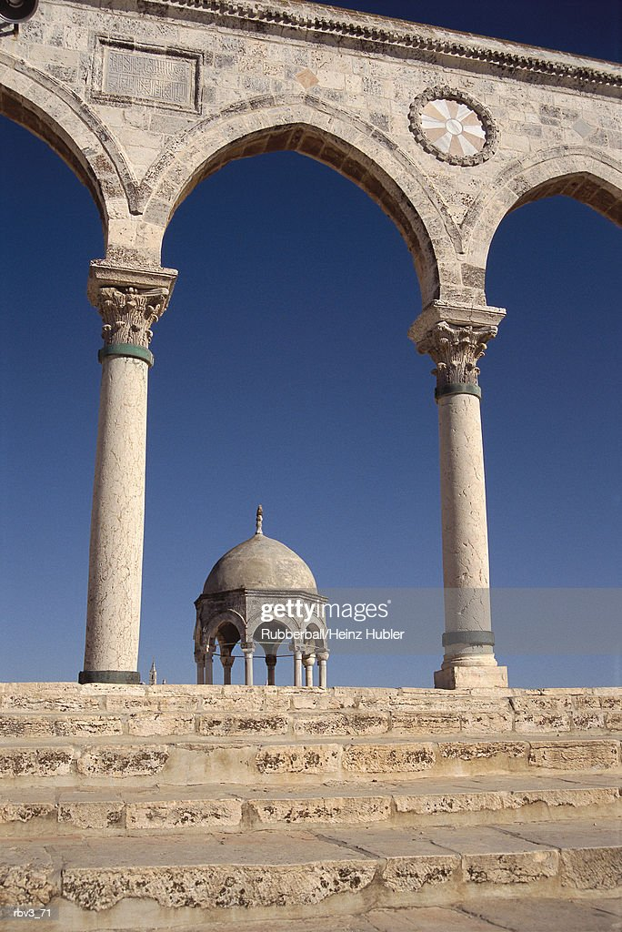 steps leading to pillars supporting arches in front of a blue sky with a gazebo in the middle : Foto de stock