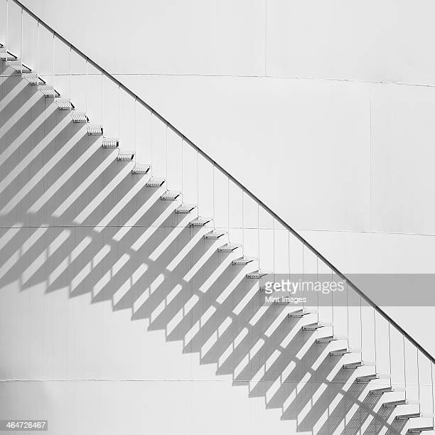 Steps leading up the side of a white storage tank at an oil refinery plant. A pattern of shadows.