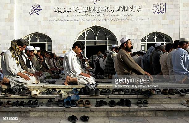 Steps of the Blue Mosque in Kabul Afghanistan are strewn with shoes as men worship during a Friday prayer service