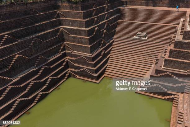 stepwell and temple pond at sri subrahmanya (subramaniya) temple,  peralassery, kannur - stepwell stock photos and pictures