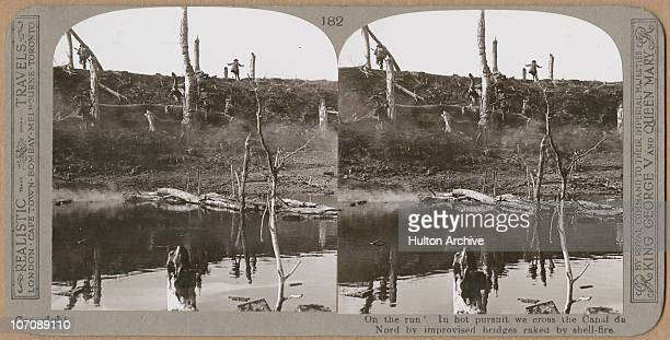 A stereo card image of Allied troops using an improvised bridge to cross the Canal du Nord during the Battle of the Canal du Nord on the outskirts of...