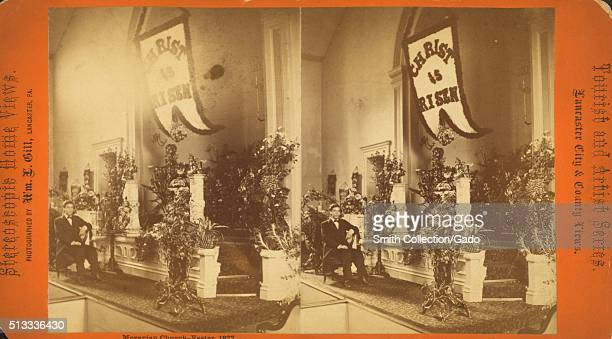A stereograph of the altar of a Moravian church the altar is covered and flowers and a banner reading 'Christ is Risen' hangs overhead as part of...