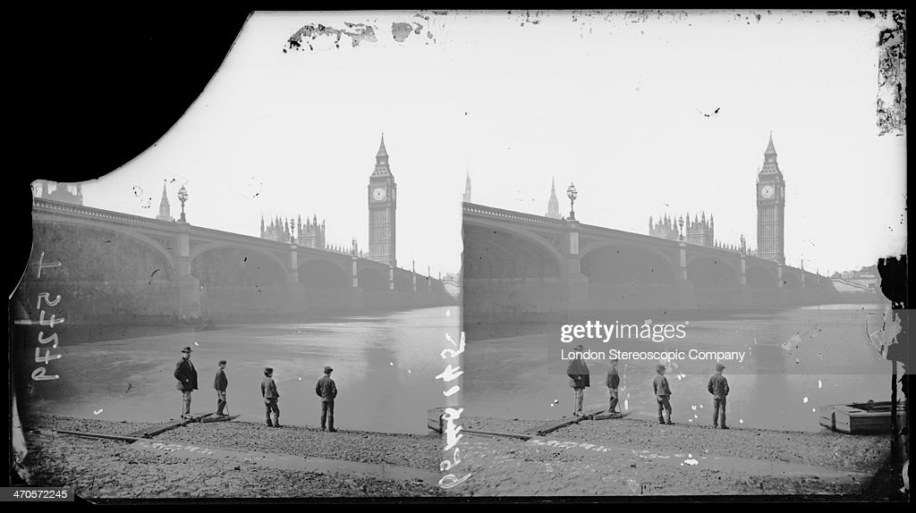 A stereoscopic image of a man and three boys standing on the south bank of the Thames, with Westminster Bridge, the Palace of Westminster and Big Ben in the background, circa 1890.